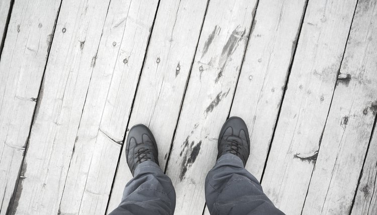 Male feet in leather shoes stand on white pier