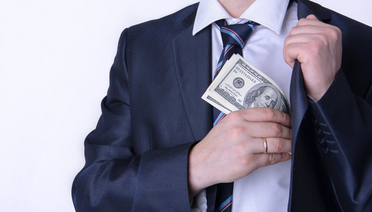 Man in suit putting money in jacket pocket