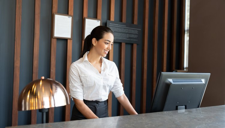 hotel receptionist checking bookings on computer system while smiling