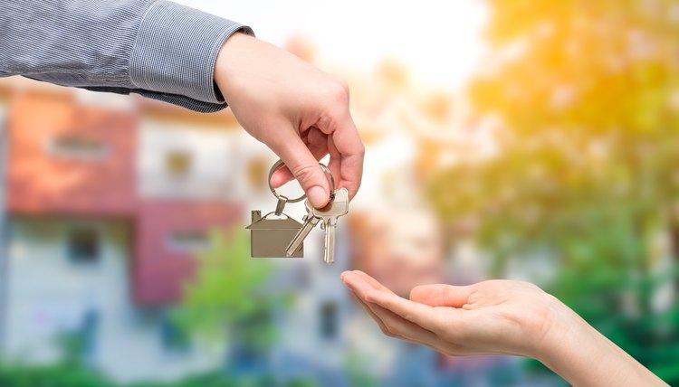 Man handing a house keys to woman