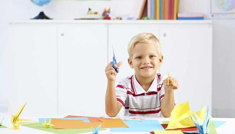 A young boy is learning how to create origami.