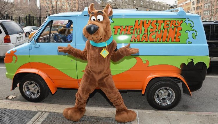 A man in a Scooby-Doo costume standing in front of a replica of the Mystery Machine van