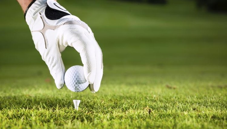 Close-up of a hand placing a golf ball on a tee