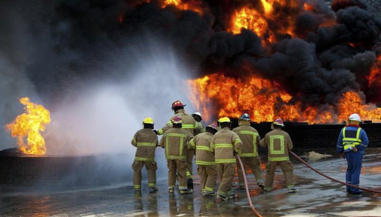 Image of a team of firefighters dousing a fire.