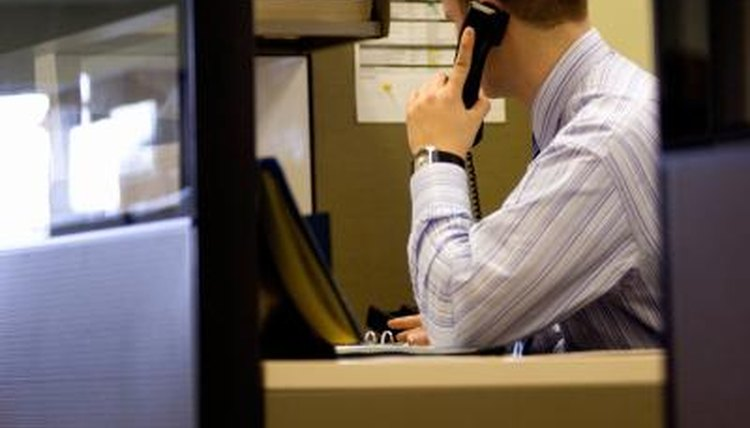 An agent on the phone in a cubical.