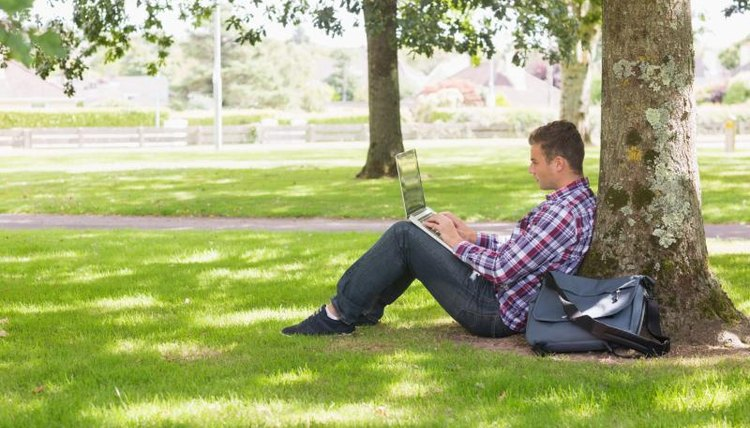 A college student working from his laptop outside.