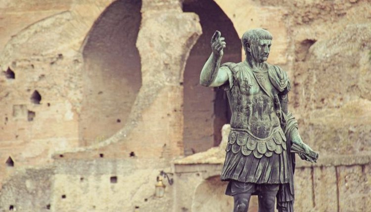 A statue of Augustus Caesar outside of an ancient building in Rome.