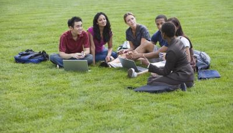 Students with a professor on a campus lawn