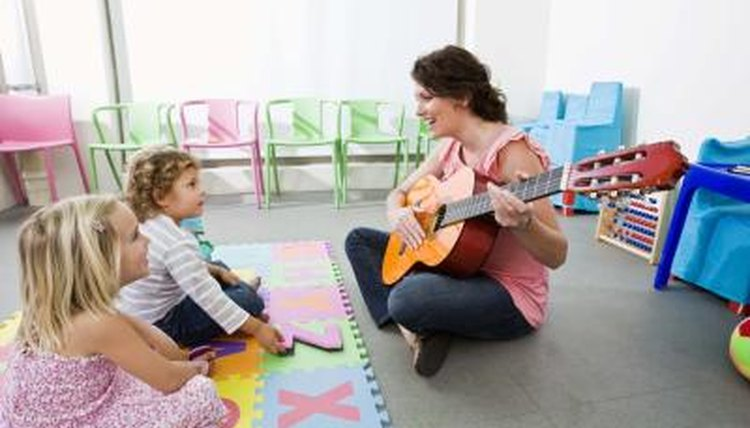 Teacher playing music for young students.