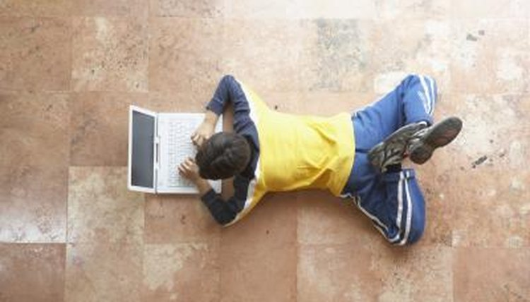A high angle view of a boy looking at a laptop on the floor.
