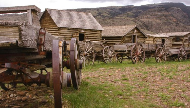 A row of cabins and wagons at a historic site along the Oregon Trail.