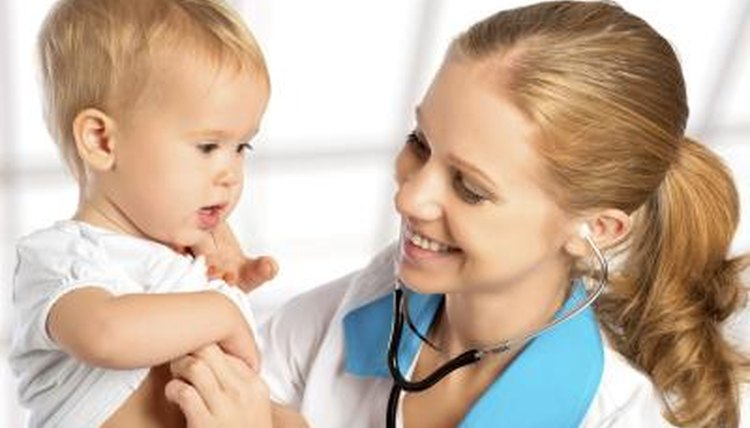 A young pediatric doctor is holding a young baby.