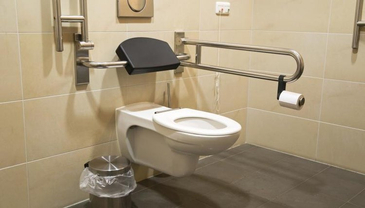 A bathroom with side rails and extended toilet seat.