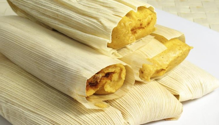 Close-up of tamales stacked on small plate.