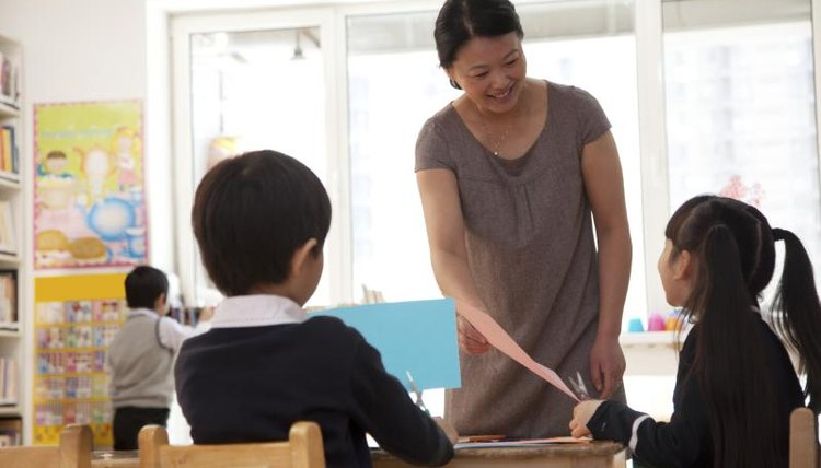 An elementary school teacher helps students with an assignment