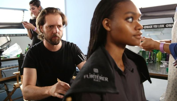 A cosmetologist assessing his client's hair in a salon.
