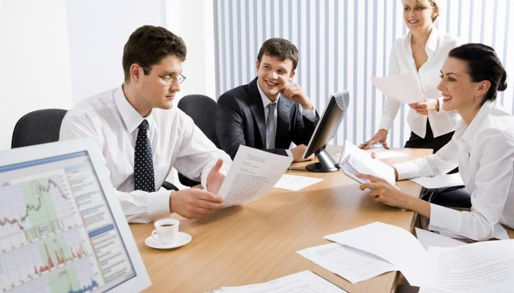 A small group of coworkers sit at one end of a table to discuss a business proposal