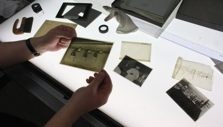 A student looking at photographs at a light table.