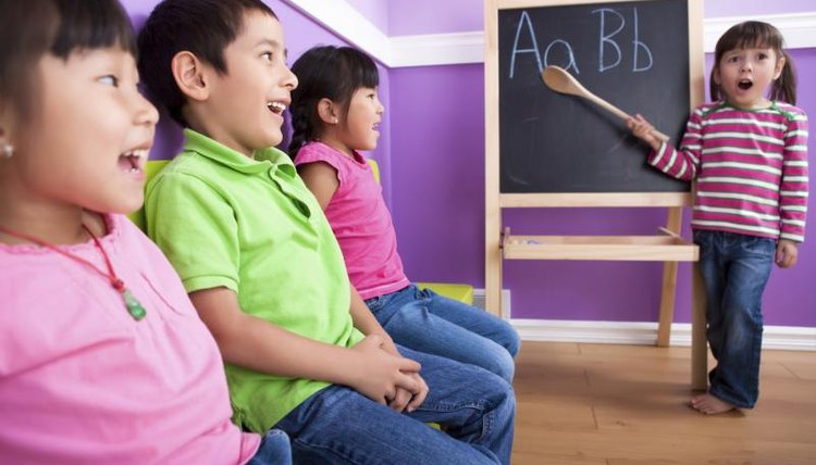 Young child pointing to a chalkboard easel.