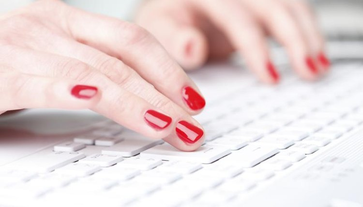 Close-up of hands typing on keyboard