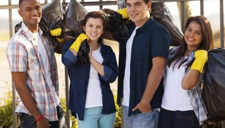A group of students wearing gloves holding garbage bags.