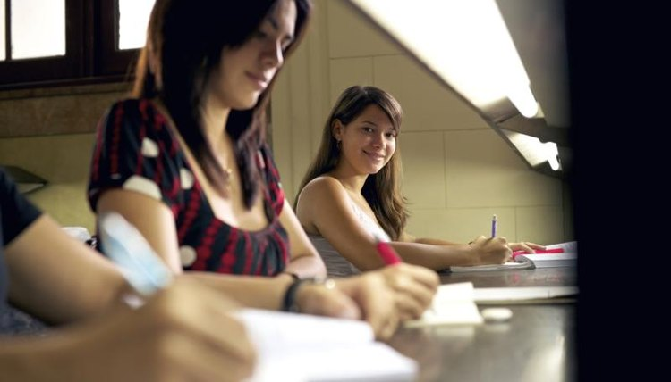 Three high school students taking a test at a table.