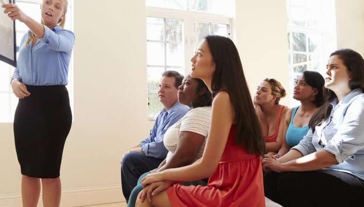 A young woman gives a presentation to a large group of adults