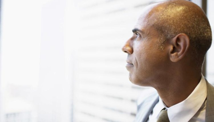A close-up of a man looking out a window.