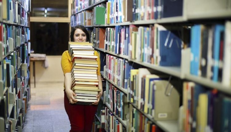 College student carries large stack of books in library