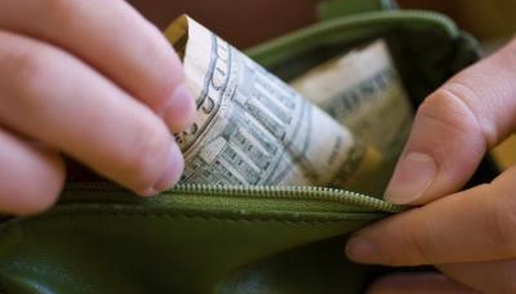 A close-up of a woman taking money out of her wallet.