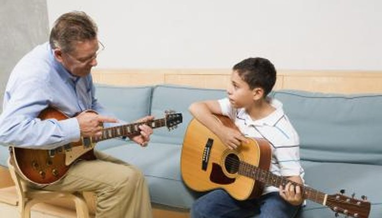 Instructor teaching young boy to play the guitar.