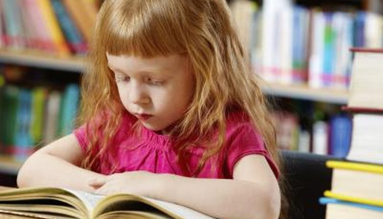 Little girl reading in library