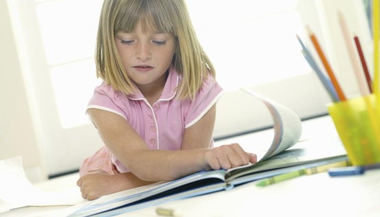 A young girl is flipping through a coloring book.