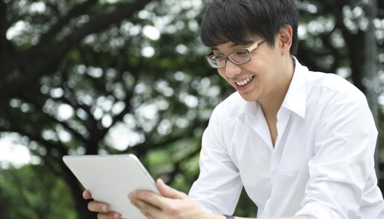 An Asian student looks at a tablet computer