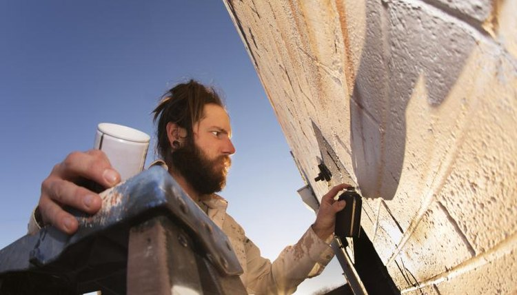 Male artist on ladder painting a wall.