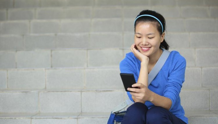 A student sits on stairs looking at her smart phone.