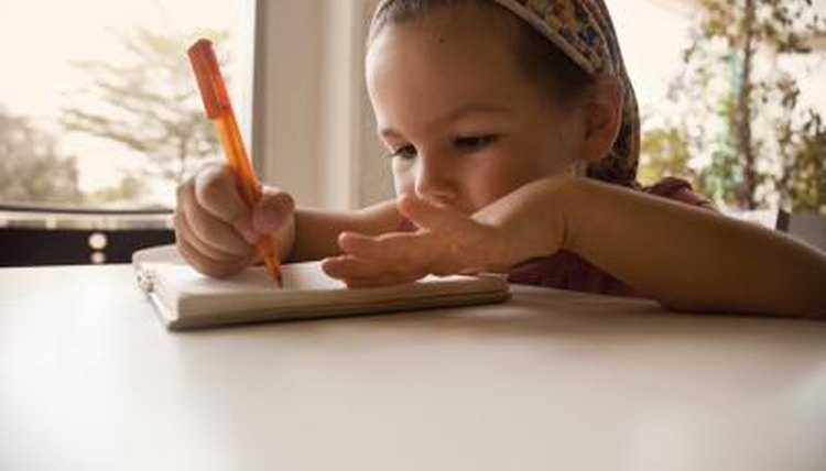 Young girl writing and smiling.