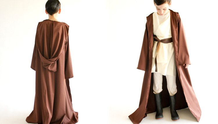 Child wearing a Star Wars Obi-wan costume with brown robe.
