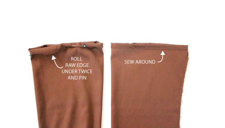 Picture of how to hem the raw edges of sleeve hems, by double rolling, pinning, and sewing in place.