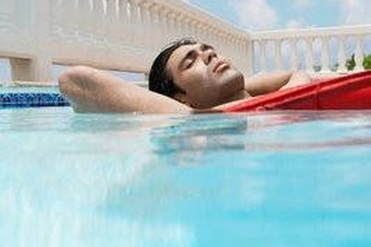 Young man on raft in pool.