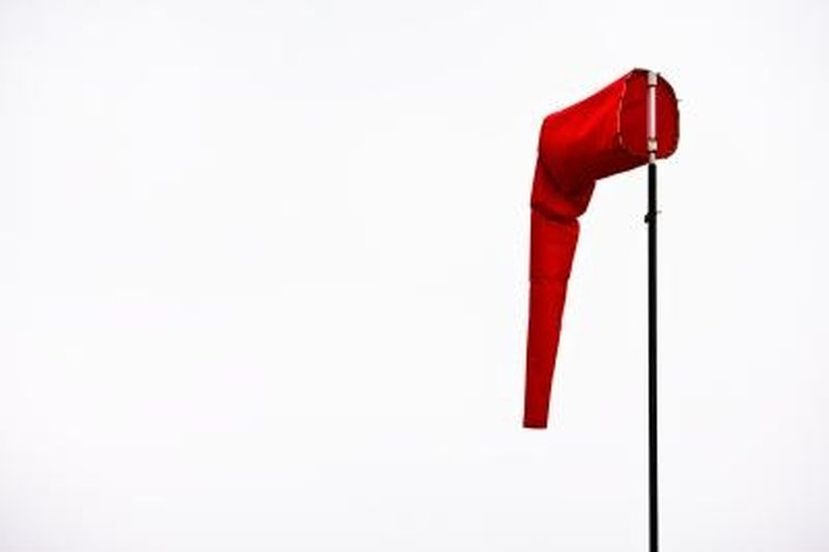 A wind sock is one useful way of determining wind direction as well as a rough speed estimate.