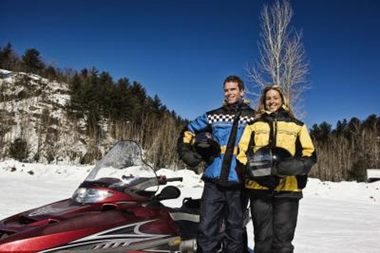 A couple holding helmets stand next to their snowmobile.