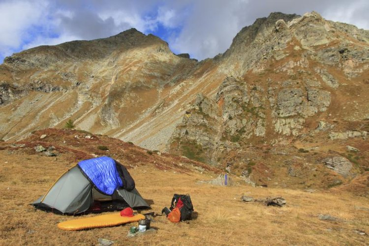 A tent, sleeping bag and backpack in front of a small mountain in autumn.