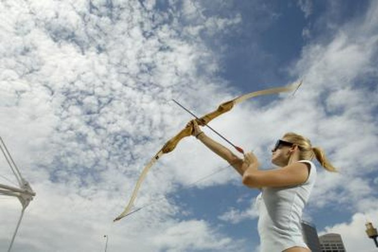 A young woman is shooting a bow and arrow.