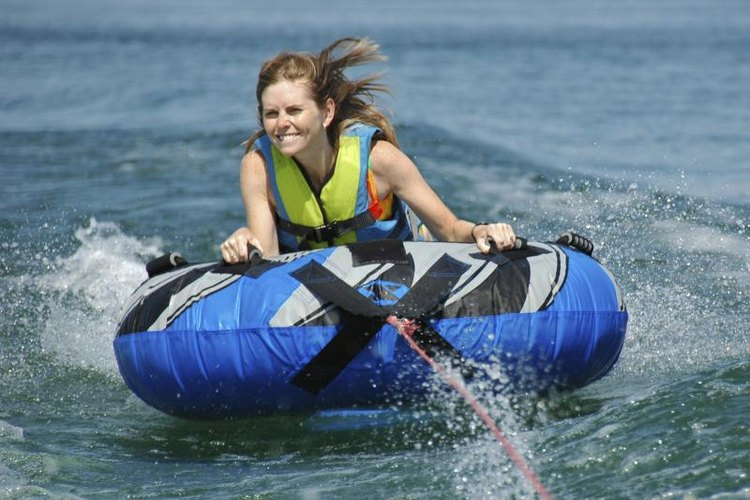 Young woman with lifejacket being pulled behind a boat while riding in a tube.
