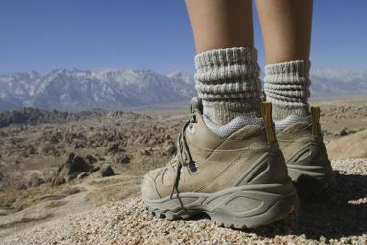 Woman wearing hiking boots in front of a mountain.