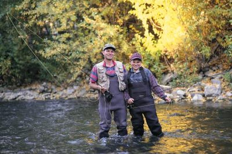 Fly fisherman and his son wearing chest waders in a river.