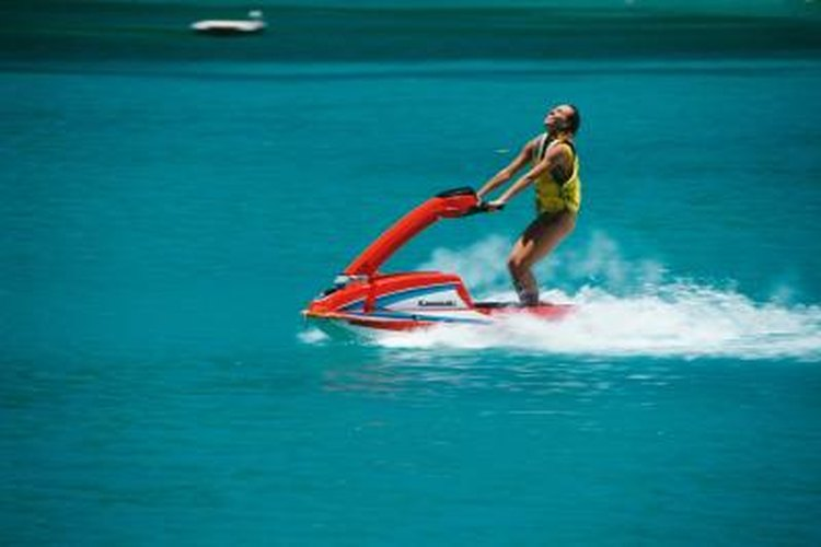 A woman on a jet ski speeds over clear blue water