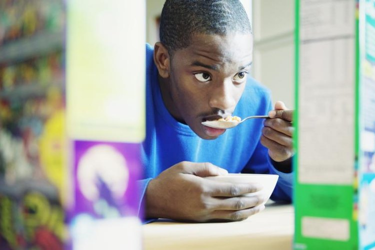 A man looks at the cereal box while he eats.