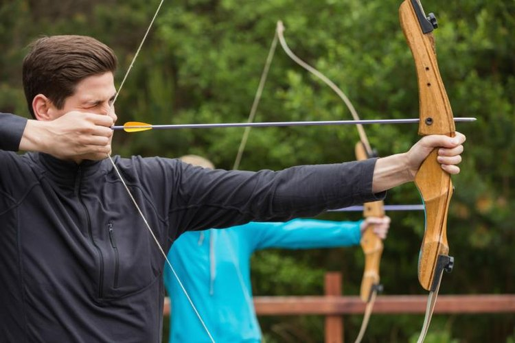 Man and woman practicing archery outside.